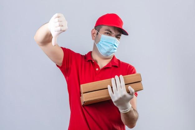 赤いポロシャツの若い配達人と分離の白い壁に嫌悪感を示すダウン親指で立っているピザの箱を保持している医療マスクのキャップ