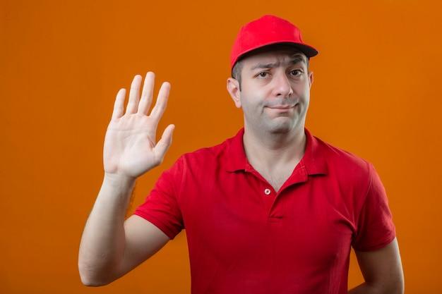 Молодой курьер в красной рубашке поло и кепке, стоящий с открытой рукой, делает знак остановки с серьезным и уверенным жестом защиты на изолированном оранжевом фоне на изолированном оранжевом