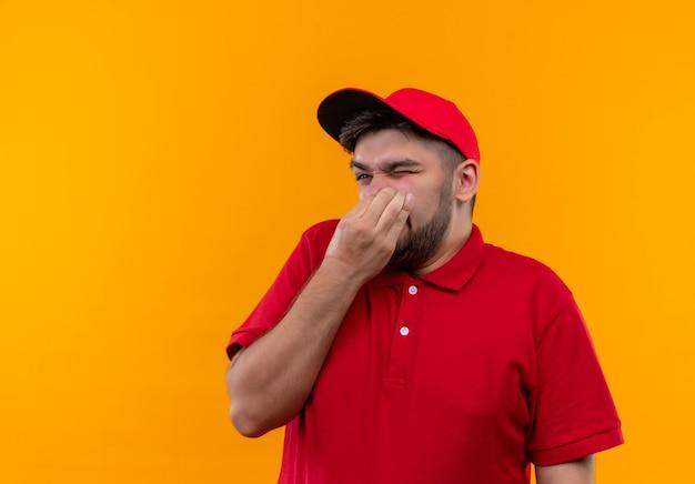赤い制服を着た若い配達人と悪臭に苦しんでいる指で鼻を閉じるキャップ