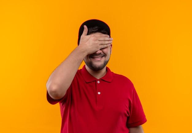 빨간 제복을 입은 젊은 배달 남자와 손으로 눈을 덮고있는 모자는 놀라움을 기다리고 웃고