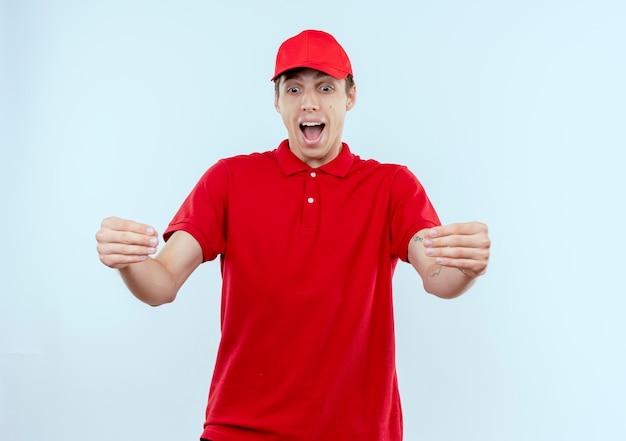 赤い制服と帽子の若い配達人は興奮し、手で幸せなジェスチャー、白い壁の上に立っているボディーランゲージの概念
