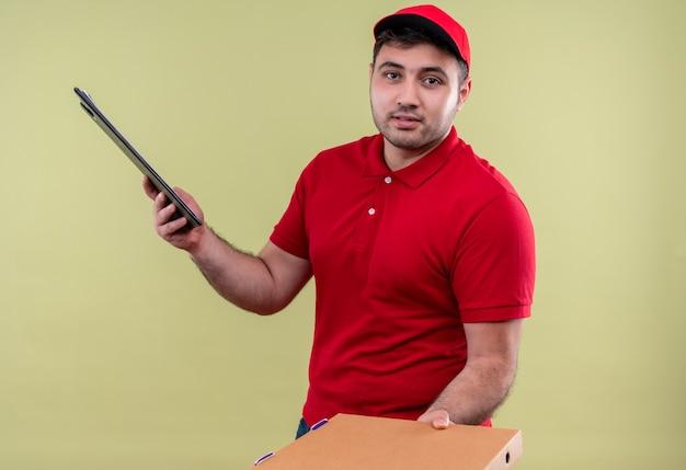 Молодой курьер в красной форме и кепке дает коробку для пиццы, держа в руках буфер обмена, дружелюбно улыбаясь, стоя над зеленой стеной
