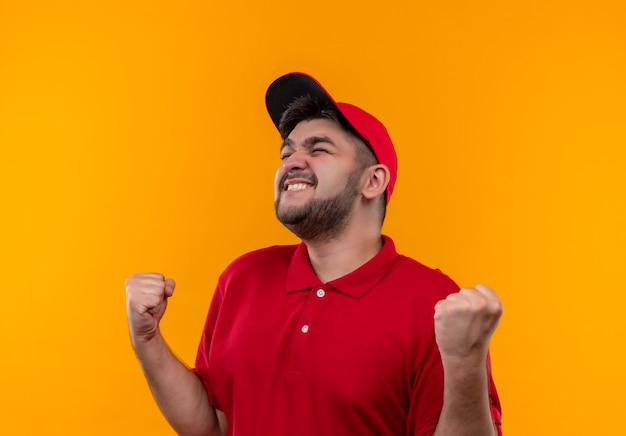 Молодой курьер в красной униформе и кепке счастлив и выходит, сжимая кулак, радуясь своему успеху