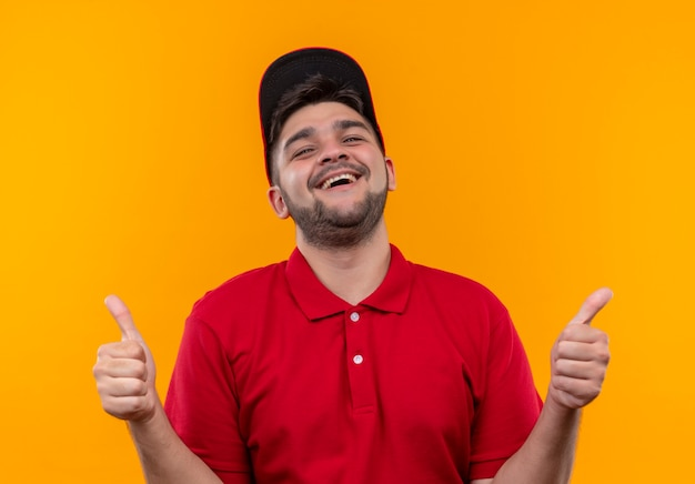 Молодой курьер в красной форме и кепке счастлив и вышел, широко улыбаясь, показывая большие пальцы руки вверх