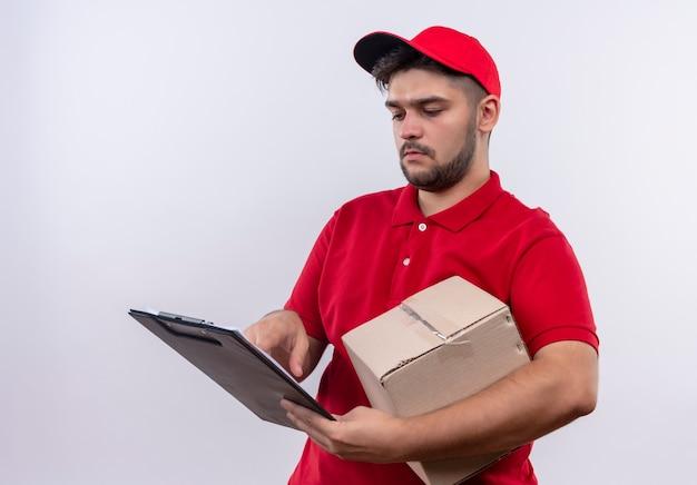 真面目な顔でそれらを見て空白のページとボックスパッケージとクリップボードを保持している赤い制服とキャップの若い配達人