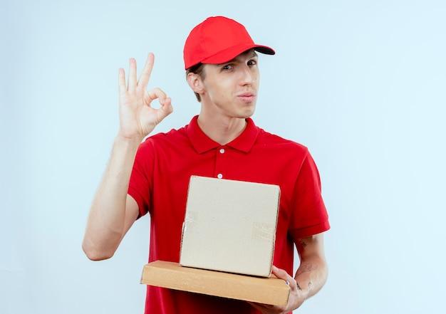Молодой курьер в красной форме и кепке, держащий коробку с пакетом и коробку для пиццы, смотрит вперед, улыбаясь, показывая знак ок, стоящий над белой стеной