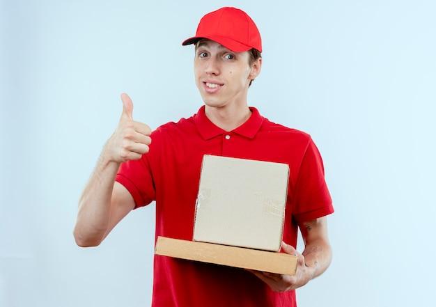 Молодой курьер в красной форме и кепке, держащий коробку, пакет и коробку для пиццы, глядя вперед, улыбаясь, показывает палец вверх, стоя над белой стеной