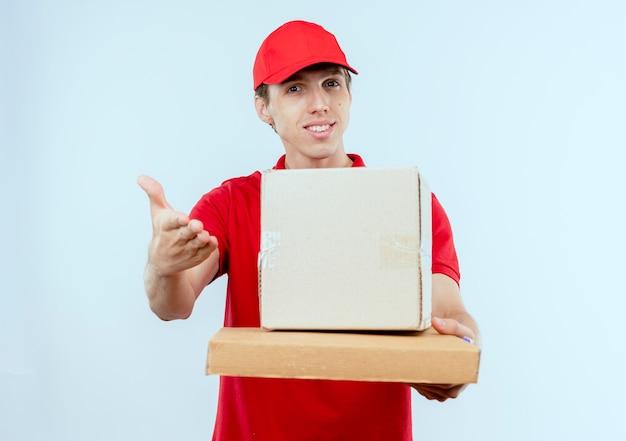 Молодой курьер в красной форме и кепке, держащий пакет коробки и коробку для пиццы, предлагающий рукой вперед, улыбаясь, стоя над белой стеной