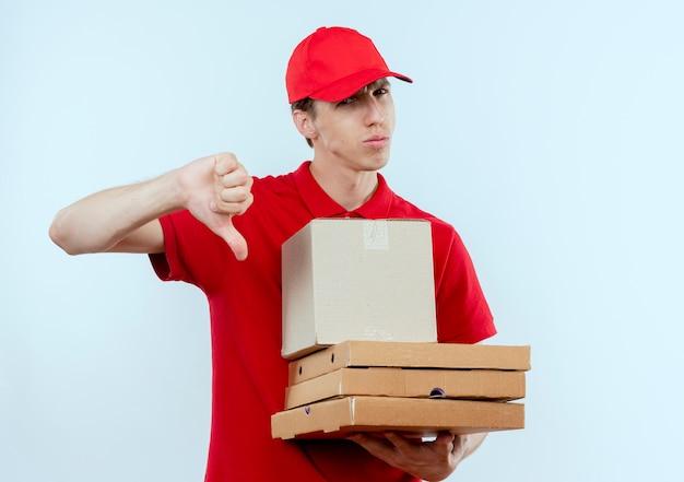 Молодой курьер в красной форме и кепке, держащий коробку с пакетом и коробки для пиццы, недовольно смотрит вперед, показывая большие пальцы вниз, стоя над белой стеной