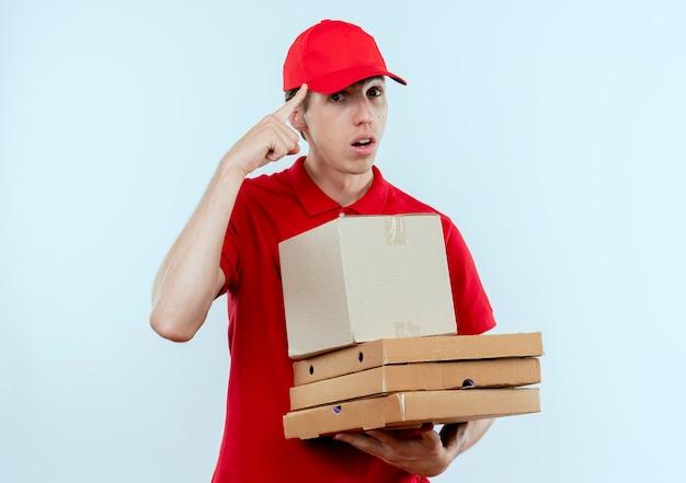 赤い制服と帽子を持った箱のパッケージとピザの箱を持った若い配達人が、白い壁の上に立っている仕事に集中して自信を持って彼の寺院を指しています