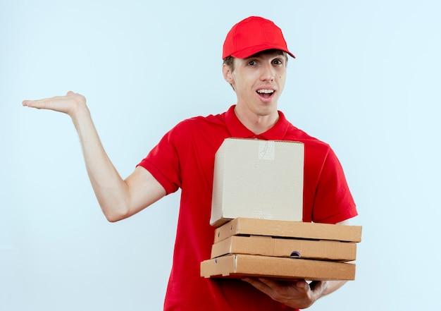 Молодой курьер в красной форме и кепке, держащий коробку с пакетом и коробки для пиццы, представляя что-то рукой, улыбаясь, стоя над белой стеной