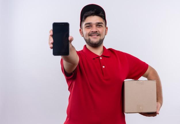 빨간 제복을 입은 젊은 배달 남자와 자신감이 미소로 카메라를보고 스마트 폰을 보여주는 상자 패키지를 들고 모자