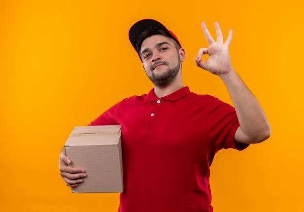 赤い制服とキャップ保持ボックスパッケージの若い配達人は、okサインを示して自信を持って笑顔