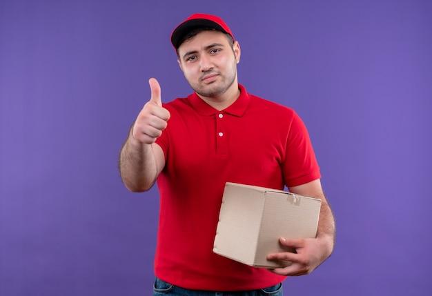 Молодой курьер в красной форме и кепке, держащий коробку с пакетом, уверенно улыбается, показывает палец вверх, стоя над фиолетовой стеной