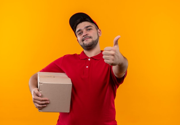 Молодой курьер в красной форме и кепке, держащий пакет коробки, уверенно улыбается, показывает палец вверх