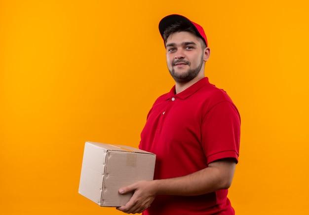 自信を持って笑顔の赤い制服とキャップ保持ボックスパッケージの若い配達人