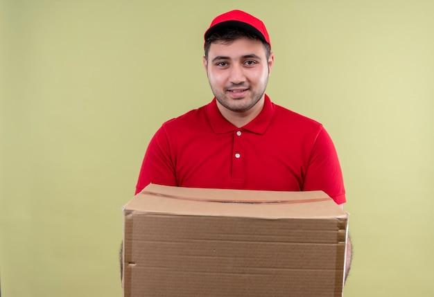 Молодой курьер в красной форме и кепке, держащий пакет коробки, дружелюбно улыбаясь, стоя над зеленой стеной