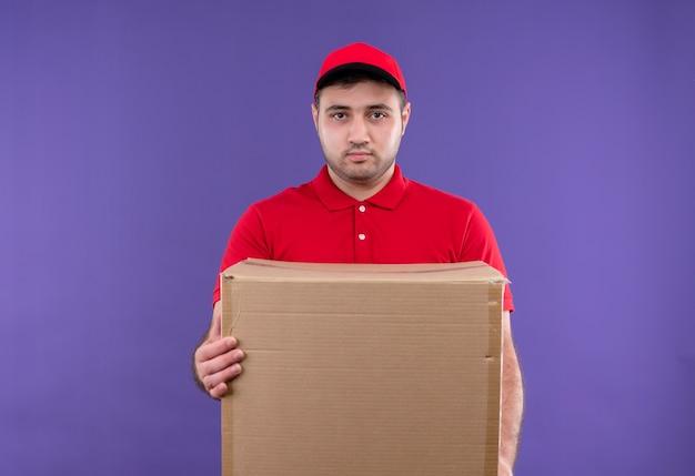 Молодой курьер в красной форме и кепке, держащий коробку с серьезным уверенным выражением лица, стоит у фиолетовой стены