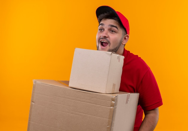 빨간 제복을 입은 젊은 배달 남자와 놀란 찾고 골판지 상자를 들고 모자