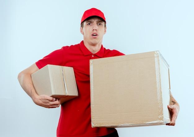 Молодой курьер в красной форме и кепке держит картонные коробки, глядя вперед, смущенный и удивленный, стоя у белой стены