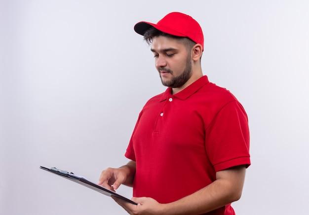 真面目な顔でそれらを見ている空白のページでクリップボードを保持している赤い制服とキャップの若い配達人