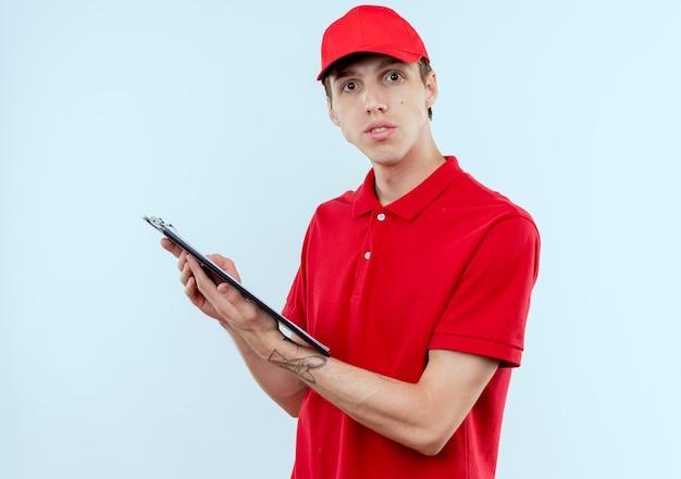 白い壁の上に立って自信を持って見える空白のページとクリップボードを保持している赤い制服と帽子の若い配達人