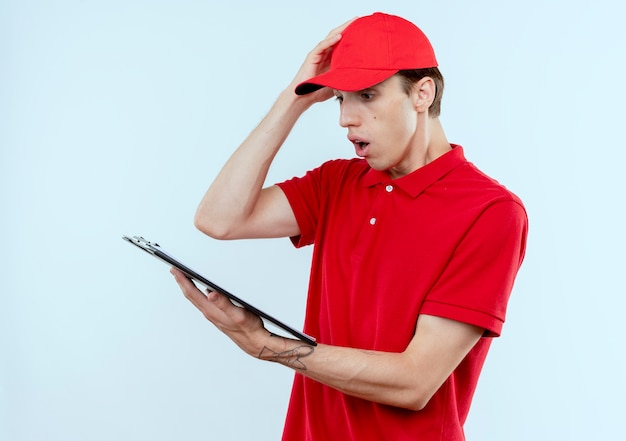 赤い制服を着た若い配達人と白い壁の上に立って混乱して驚いたように見える空白のページでクリップボードを保持しているキャップ