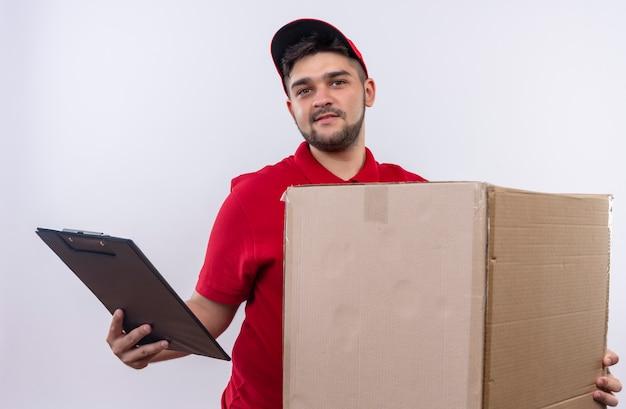 빨간 제복을 입은 젊은 배달 남자와 큰 상자 패키지 및 클립 보드를 들고 얼굴에 미소로 자신감을 찾고