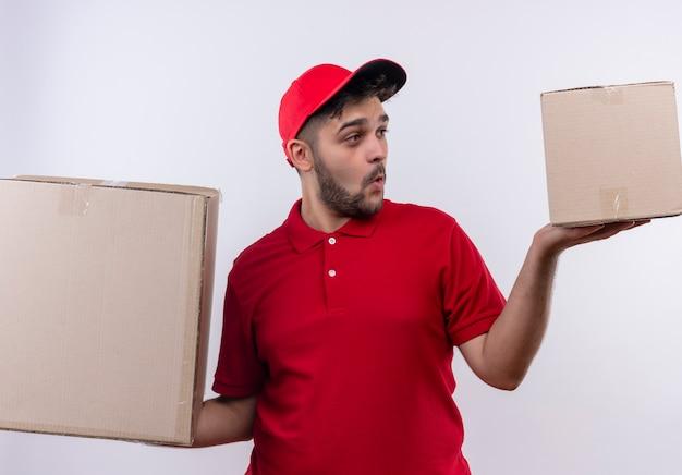Молодой курьер в красной униформе и кепке держит большие картонные коробки, выглядит озадаченным, пытаясь сделать выбор