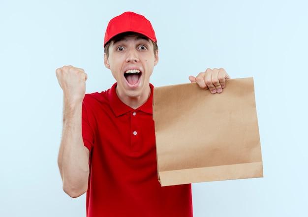 赤い制服を着た若い配達人と白い壁の上に立って幸せで興奮した拳を握り締める紙のパッケージを保持しているキャップ