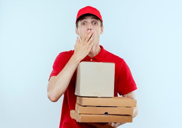Молодой курьер в красной форме и кепке, держащий коробки для пиццы и коробочный пакет, выглядит удивленным и удивленным, стоя над белой стеной