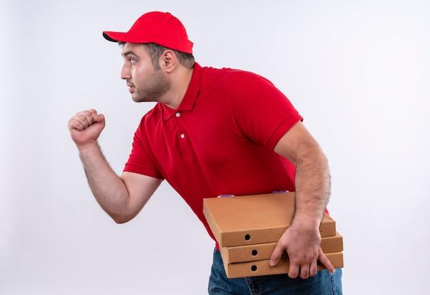 赤い制服を着た若い配達人と白い壁に真面目な顔で横に立っている拳を握り締めるピザの箱を保持しているキャップ