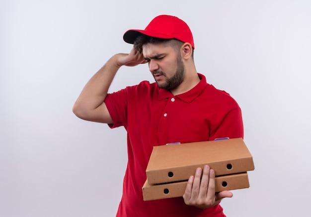 赤い制服を着た若い配達人とピザの箱を持って疲れて過労に見える頭に触れると頭痛が強い