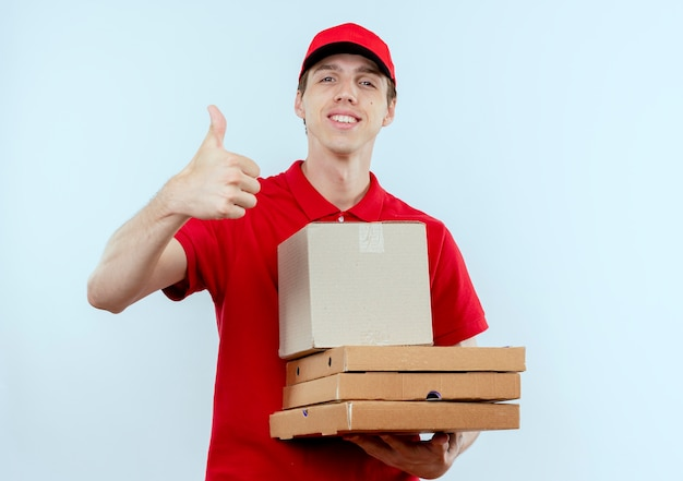Молодой курьер в красной форме и кепке держит коробки для пиццы, глядя вперед, улыбаясь, уверенно показывая большие пальцы руки вверх, стоя над белой стеной