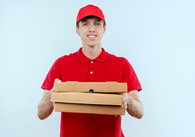 Молодой курьер в красной форме и кепке держит коробки для пиццы, глядя вперед с уверенным выражением лица, стоя над белой стеной