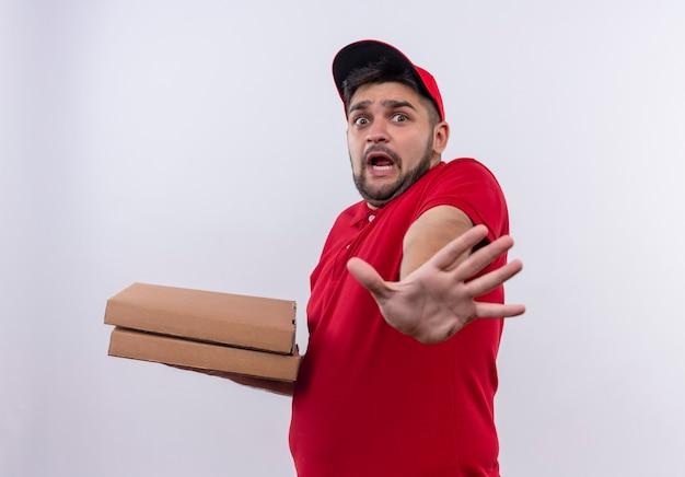 Молодой курьер в красной форме и кепке держит коробки для пиццы, делая знак остановки с испуганной рукой