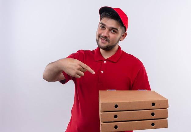 赤い制服と帽子を持った若い配達人が自信を持って笑ってそれに指で指しているピザの箱を保持しています