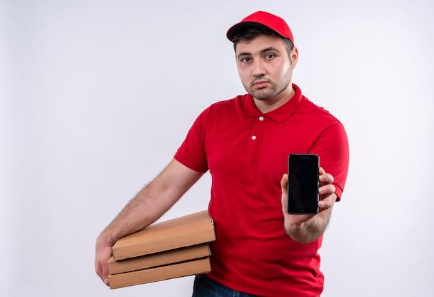 白い壁の上に立っている自信を持って表情でスマートフォンを示すピザの箱を保持している赤い制服と帽子の若い配達人