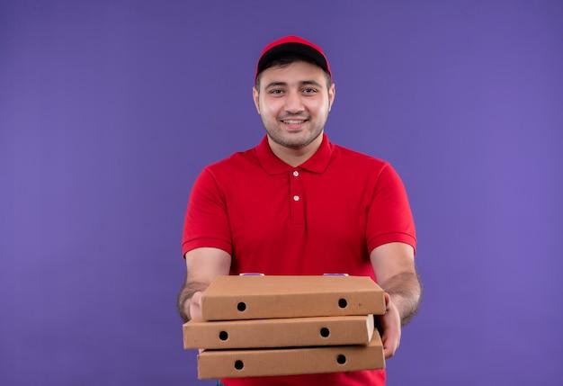 Молодой курьер в красной форме и кепке держит коробки для пиццы, весело улыбаясь, стоя у фиолетовой стены