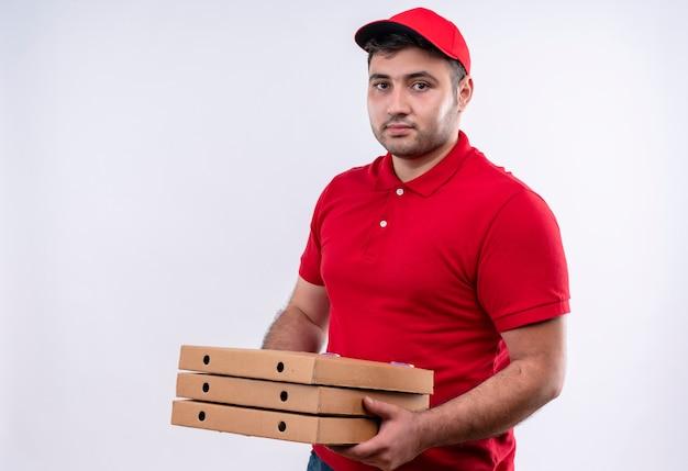 白い壁の上に立っている自信を持って表情で笑ってピザの箱を保持している赤い制服と帽子の若い配達人
