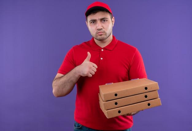 Молодой курьер в красной форме и кепке держит коробки для пиццы с нахмуренным лицом, показывая пальцы вверх, стоя над фиолетовой стеной