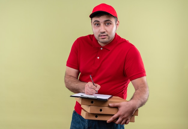 Молодой курьер в красной форме и кепке, держащий коробки для пиццы, пишет на пустой странице, дружелюбно улыбаясь, стоя над зеленой стеной