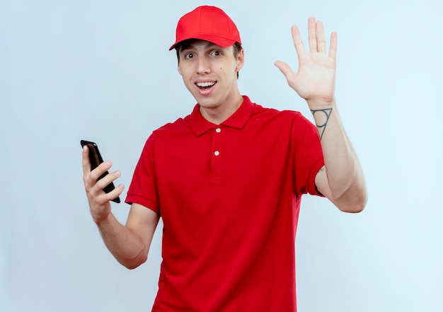 赤い制服と白い壁の上に立っている手で手を振って正面を見てスマートフォンを保持している帽子の若い配達人