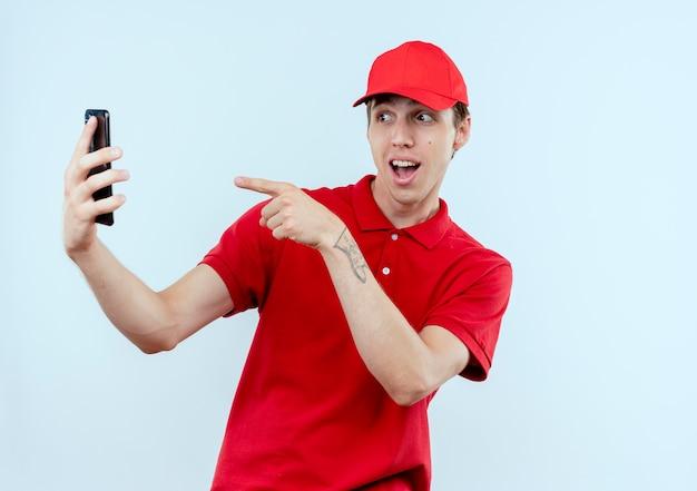 Молодой курьер в красной форме и кепке держит смартфон, принимая селфи, улыбаясь, указывая пальцем на камеру своего смартфона, стоящую над белой стеной