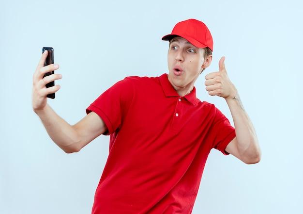 Молодой курьер в красной форме и кепке держит смартфон, делающий селфи, улыбаясь, показывает палец вверх, стоя над белой стеной