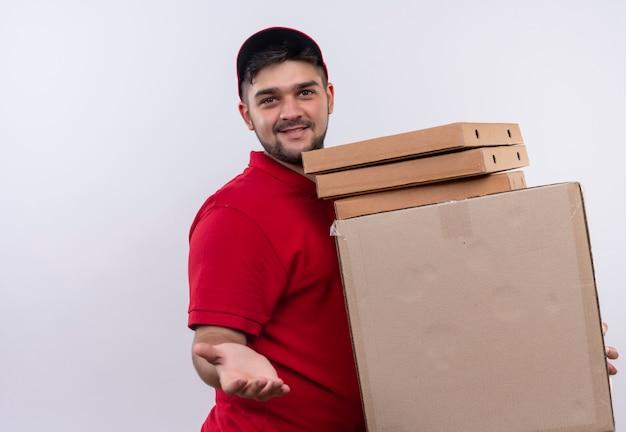 빨간 제복을 입은 젊은 배달 남자와 친절한 미소를 제공하는 손을 제공하는 상자의 스택을 들고 모자