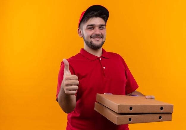 赤い制服を着た若い配達人とピザの箱のスタックを保持している自信を持って笑顔を見て親指を表示