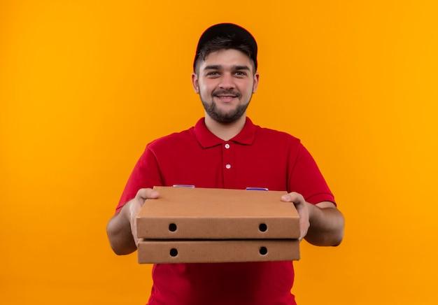 Молодой курьер в красной форме и кепке держит стопку коробок для пиццы, уверенно улыбаясь Бесплатные Фотографии