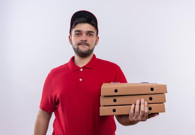 赤い制服を着た若い配達人と自信を持って笑顔に見えるピザの箱のスタックを保持しているキャップ