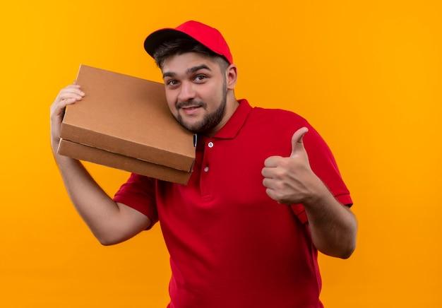 Молодой курьер в красной форме и кепке, держащий стопку коробок для пиццы, показывает палец вверх улыбается